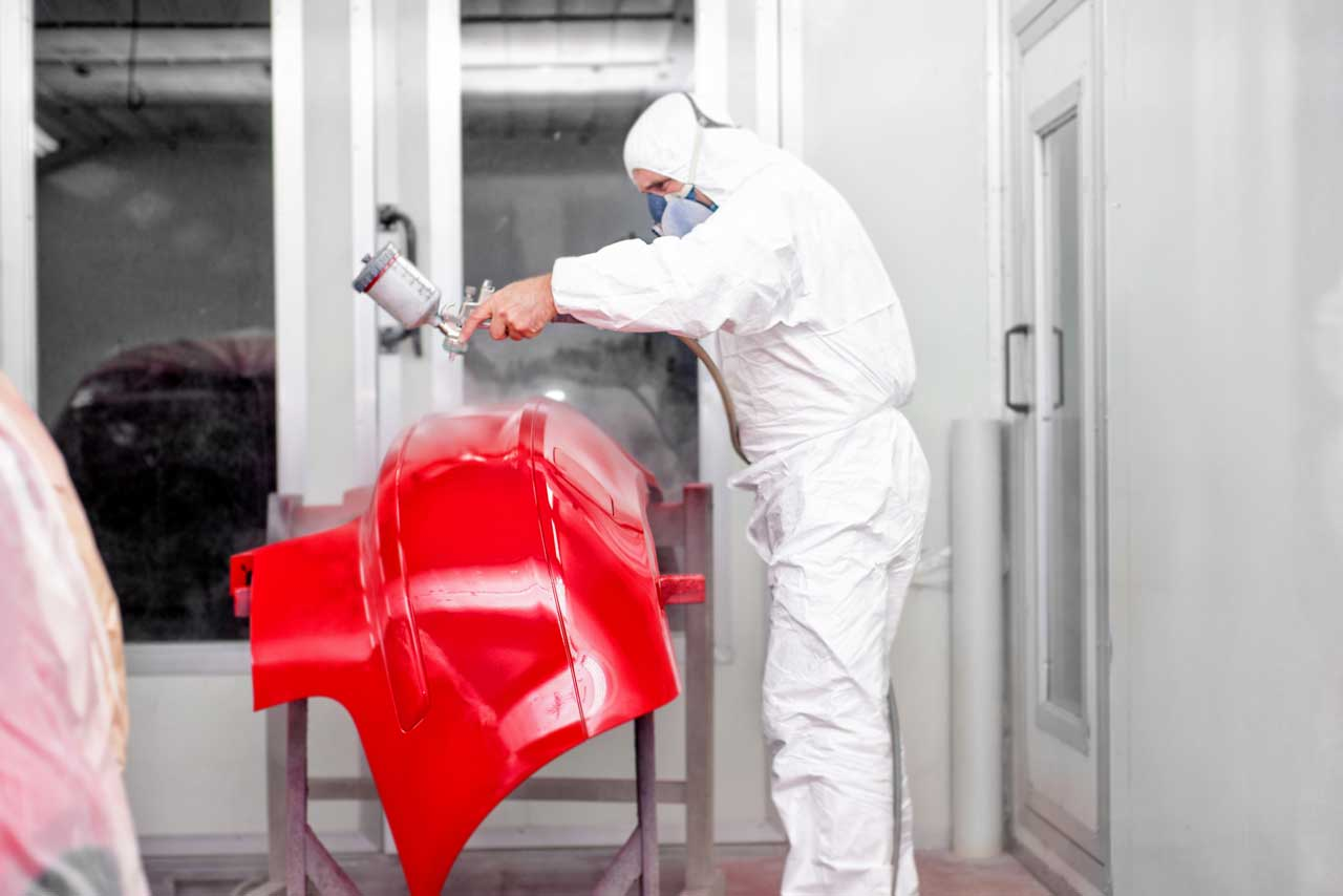 St-Louis-auto-body-worker-spraying-red-paint